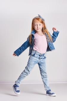 Russia ekaterinburg -,: bambina con i capelli rossi, bei capelli lunghi. bambino della testarossa che posa su una luce, scuola del modello di moda. gioia e divertimento