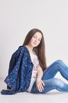 Russia ekaterinburg -,: moda ragazza divertente in jeans in posa su un bianco. scuola modello per bambini. bella ragazza sorridente. estate