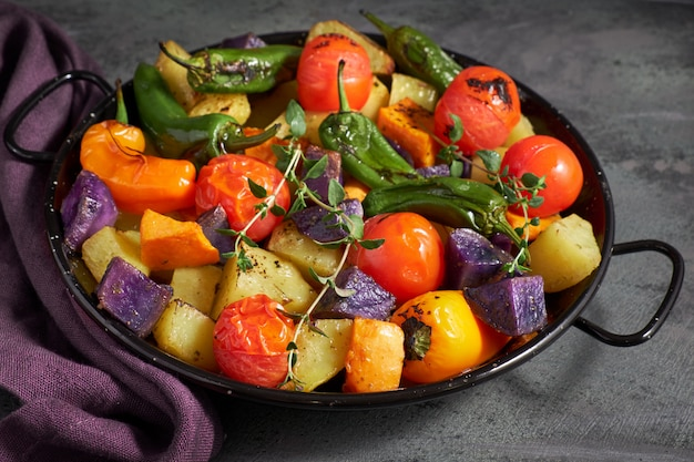 Rustico, verdure al forno in teglia. pasto vegano vegetariano stagionale su oscurità con un asciugamano di lino