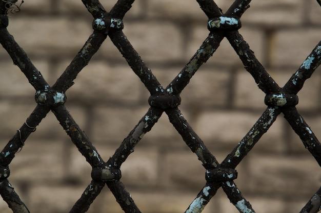 Rusty chain link fence sul primo piano astratto grigio e nero del fondo grigio, di un fondo del collegamento a catena