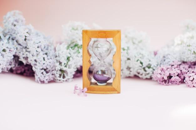 Sabbia che attraversa le lampadine di una clessidra che misura il tempo che passa in un conto alla rovescia ad una scadenza, su una priorità bassa della sorgente del lillà del fiore con lo spazio della copia.