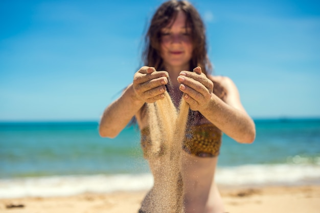 Sabbia commovente della ragazza sulla spiaggia