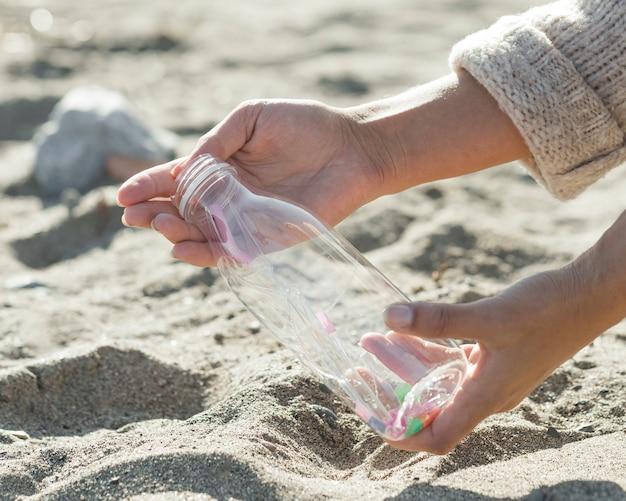 Sabbia di pulizia della donna del primo piano della bottiglia di plastica