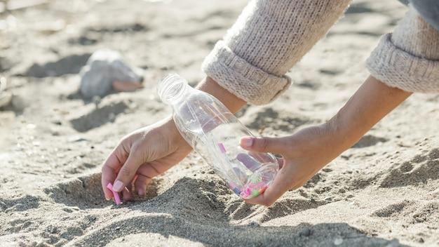 Sabbia di pulizia della donna del primo piano della bottiglia