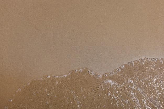 Sabbia fine liscia e acqua limpida con bolle.
