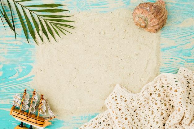 Sabbia fra la foglia della pianta vicino alla conchiglia e la nave del giocattolo a bordo