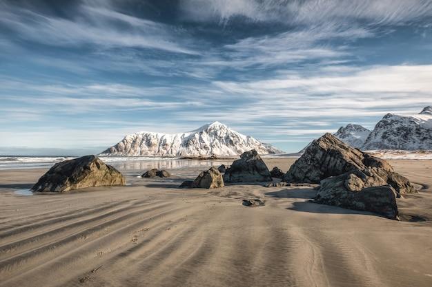 Sabbia naturale del solco con la montagna e il cielo blu della neve alla spiaggia di skagsanden