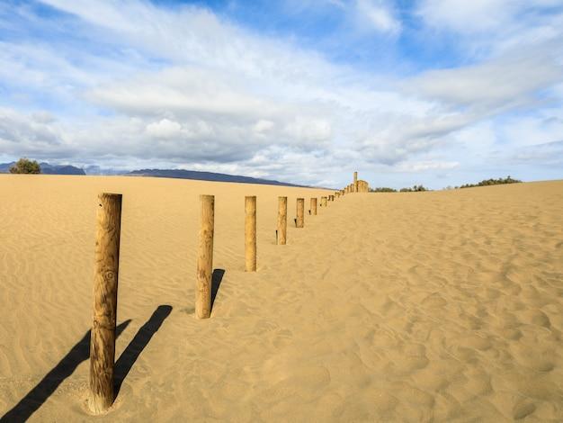 Sabbia tra le dune di maspalomas, un piccolo deserto a gran canaria. sabbia e cielo, e una staccionata di legno che segna l'area proibita della riserva naturale di uccelli la charca.