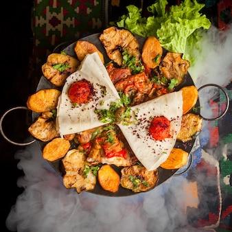 Sacca di pollo vista dall'alto con patate fritte e pomodoro e lavash in fumo