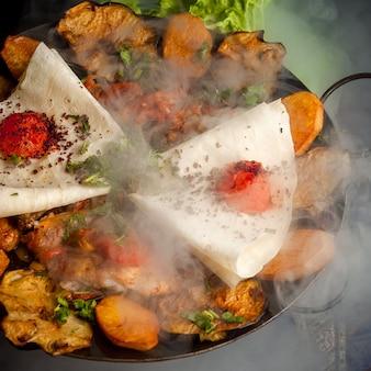 Sacca di pollo vista laterale con patate fritte e pomodoro e lavash in fumo