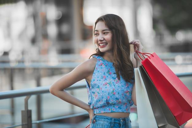 Sacchetti della spesa asiatici della tenuta della donna e mani sollevate su