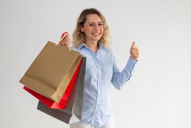 Sacchetti della spesa della tenuta della donna positiva e mostrare pollice in su