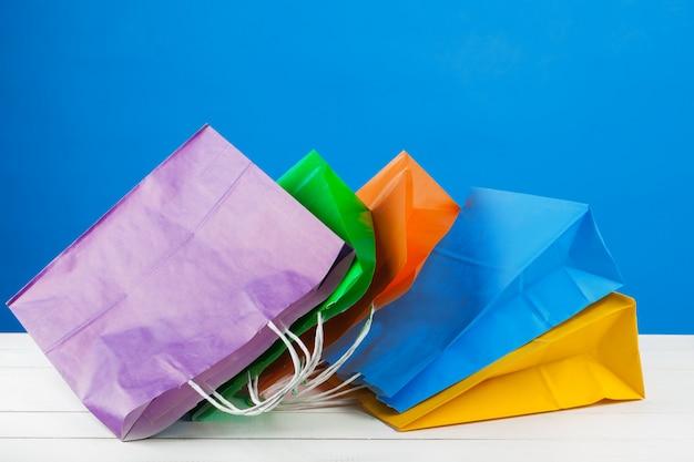 Sacchetti della spesa di carta con lo spazio della copia su fondo blu