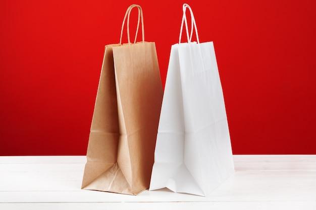 Sacchetti della spesa di carta con lo spazio della copia su fondo rosso