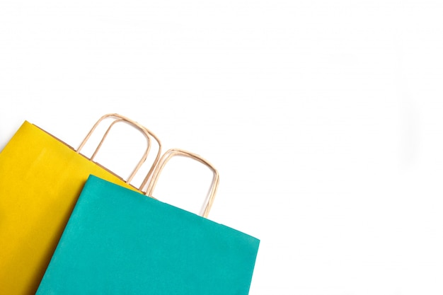 Sacchetti della spesa di carta gialla e verde isolati.