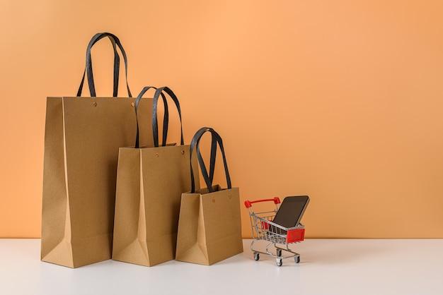 Sacchetti della spesa e carrello o carrello di carta con lo smartphone sulla tavola bianca e sulla parete arancio pastello