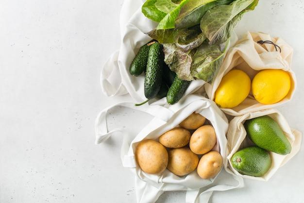 Sacchetti della spesa ecologici del tessuto con le frutta e le verdure su fondo bianco