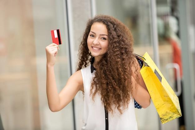 Sacchetti della spesa graziosi della tenuta della donna e mostrare la carta di credito in bianco