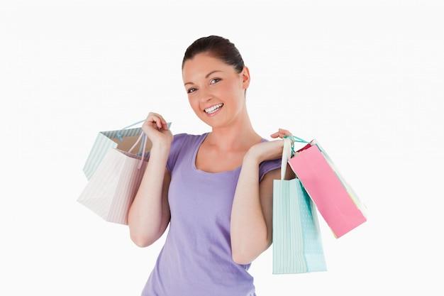 Sacchetti della spesa graziosi della tenuta della donna mentre stando