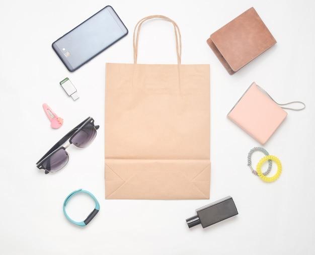 Sacchetti di carta e molti acquisti di gadget e accessori su uno sfondo bianco: occhiali da sole, smartphone, braccialetto intelligente, banca powel, chiavetta usb, portafoglio. concetto di consumatore. vista dall'alto.