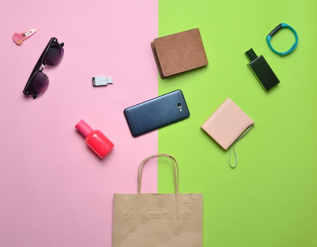 Sacchetti di carta e molti acquisti di gadget e accessori su uno sfondo colorato: occhiali da sole, smartphone, braccialetto intelligente, banca powel, chiavetta usb, portafoglio. concetto di consumatore. vista dall'alto.