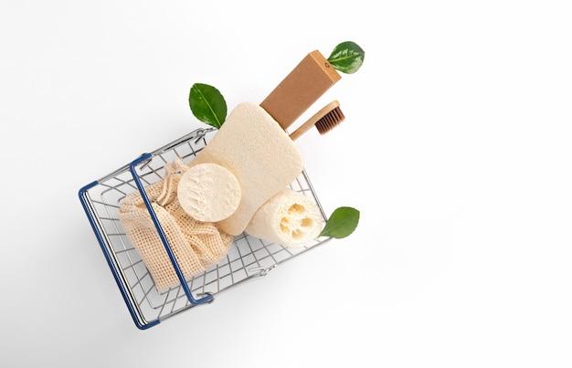 Sacchetti di cotone eco, spazzolini da denti di bambù, spugna di luffa in un cestino del supermercato in metallo su uno sfondo bianco con spazio di copia. isolato. nessun acquisto di cibo. vita senza sprechi. concetto di shopping ecologico