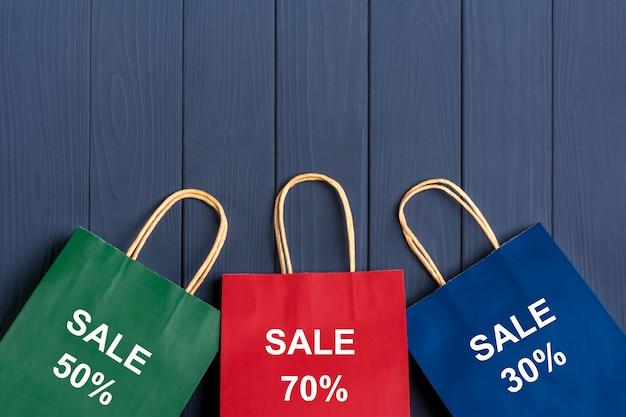 Sacchetti per imballaggio multicolore 30%, 70%, 50% su sfondo grigio scuro vista dall'alto