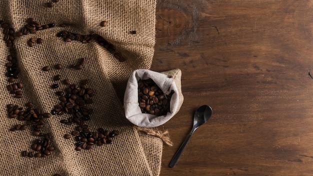 Sacchetto con caffè e cucchiaio vicino a fagioli