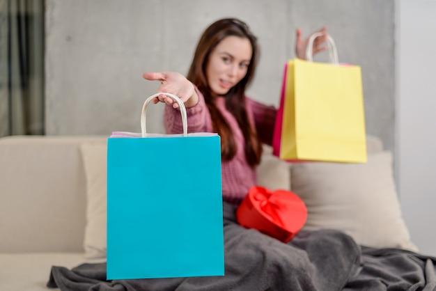 Sacchetto della spesa blu luminoso a fuoco, ragazza che tiene i sacchetti variopinti e una scatola in forma di cuore su un fondo