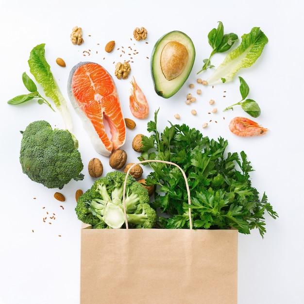 Sacchetto della spesa con alimento sano su fondo bianco con la vista superiore dello spazio della copia