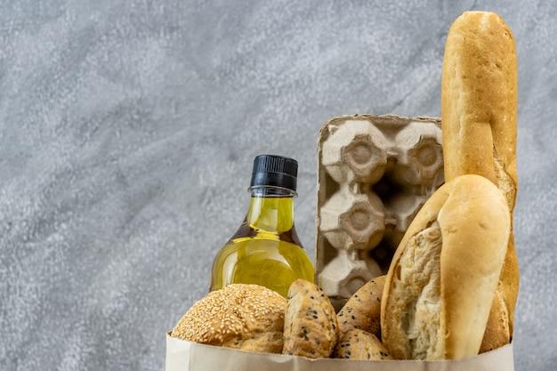 Sacchetto della spesa con uovo da cucina olio e varietà di pane in sacchetto di carta usa e getta su sfondo grigio loft vintage. concetto di cibo e bevande e generi alimentari da forno per la consegna.
