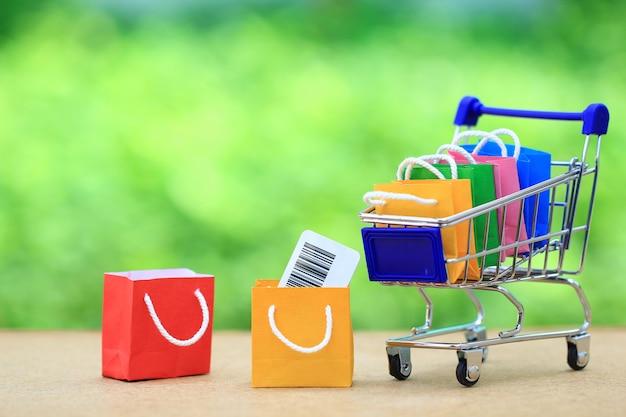 Sacchetto della spesa di carta sul carrello miniatura di modello, concetto di acquisto