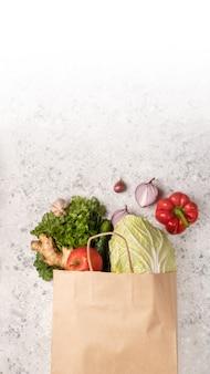 Sacchetto della spesa di uso di giorno di eco con la spesa di drogheria delle verdure in supermercato.