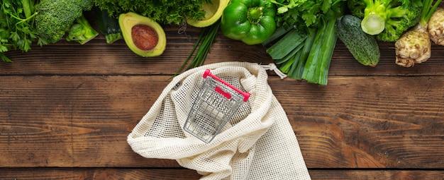 Sacchetto della spesa di vista superiore con il piccolo carrello e cibo pulito dell'alimento sano. verdura verde sulla vista di legno del piano d'appoggio