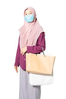 Sacchetto della spesa musulmano della tenuta della donna isolato su spazio bianco.