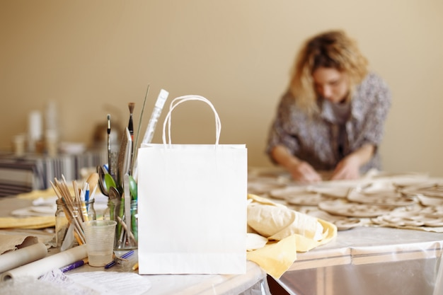 Sacchetto di carta bianco sullo sfondo dell'officina e la ragazza che produce prodotti in argilla