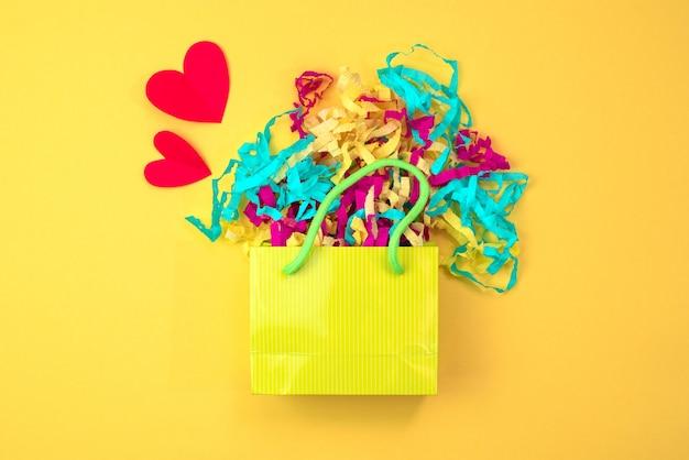Sacchetto di carta con stelle filanti colorate su uno sfondo giallo brillante