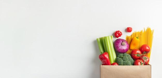 Sacchetto di carta di diversi alimenti sani su un tavolo.