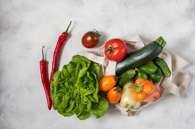 Sacchetto di carta e cotone di verdure sane, piatti piatti sul tavolo. vista dall'alto, copia spazio.