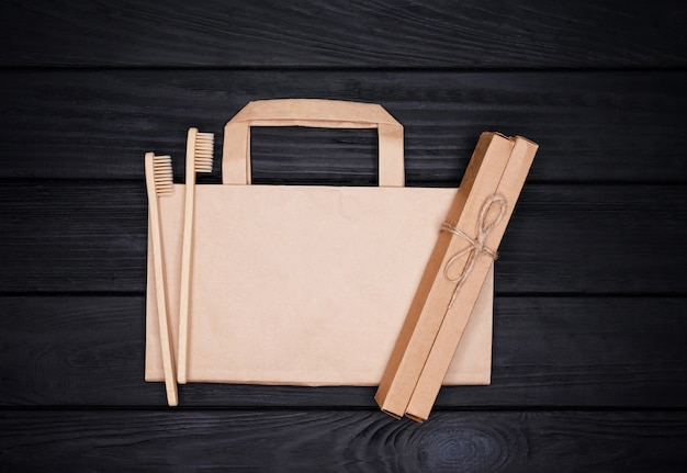 Sacchetto di carta kraft naturale eco flatlay e spazzolini da denti in bambù su fondo nero