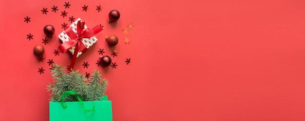 Sacchetto di carta verde di natale con acquisti di regali e vacanze su rosso.