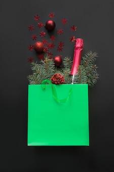 Sacchetto di carta verde shopping natalizio con bottiglia di champagne e acquisti per le vacanze