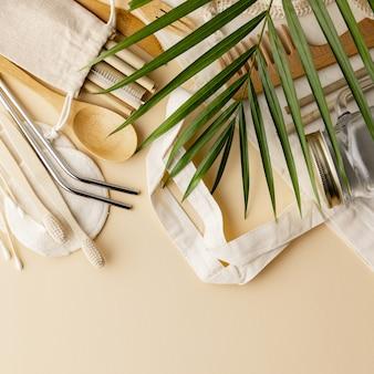 Sacchetto di cotone, cultery di bambù, vaso di vetro, spazzolini da denti di bambù, spazzola per capelli e cannucce su sfondo colorato, piatto lay.