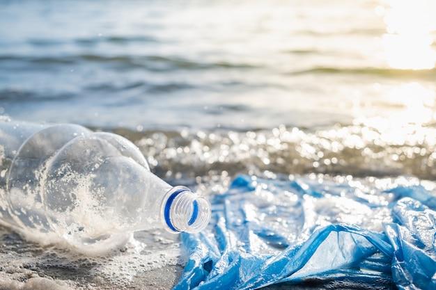 Sacchetto di plastica e bottiglie sul concetto di inquinamento della spiaggia, della spiaggia e dell'acqua.