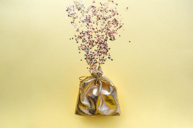 Sacchetto regalo di tessuto dorato su sfondo giallo. caramelle multicolori.