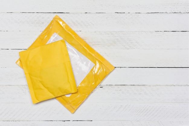 Sacchi di carta gialli dai negozi online cinesi su fondo di legno bianco, vista dall'alto con spazio di copia