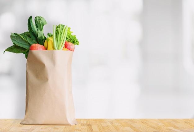 Sacco di carta con cibo sano su sfondo bianco