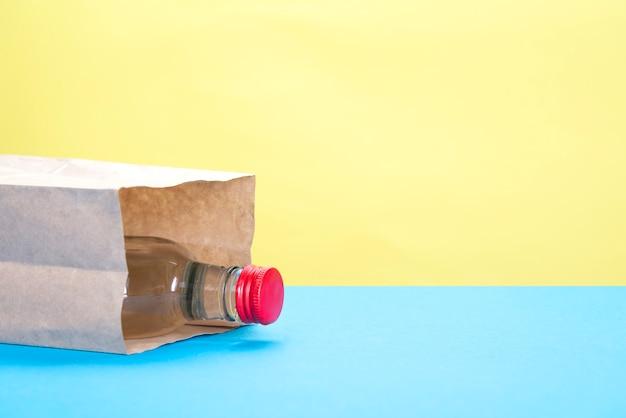 Sacco di carta con una bottiglia di alcool su giallo e blu
