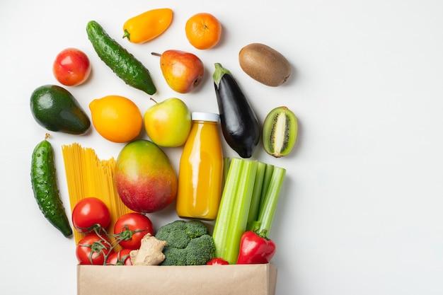 Sacco di carta di diversi alimenti naturali su un tavolo.