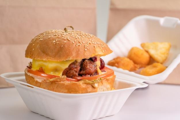 Sacco di carta e scatola dell'hamburger sulla tavola isolata su una parete bianca, primo piano